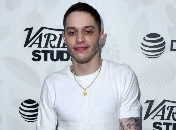 Pete smiles while wearing a white T-shirt to an event