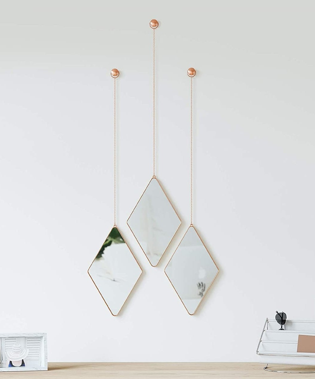 three diamond shaped mirrors hanging from dainty chains on a wall