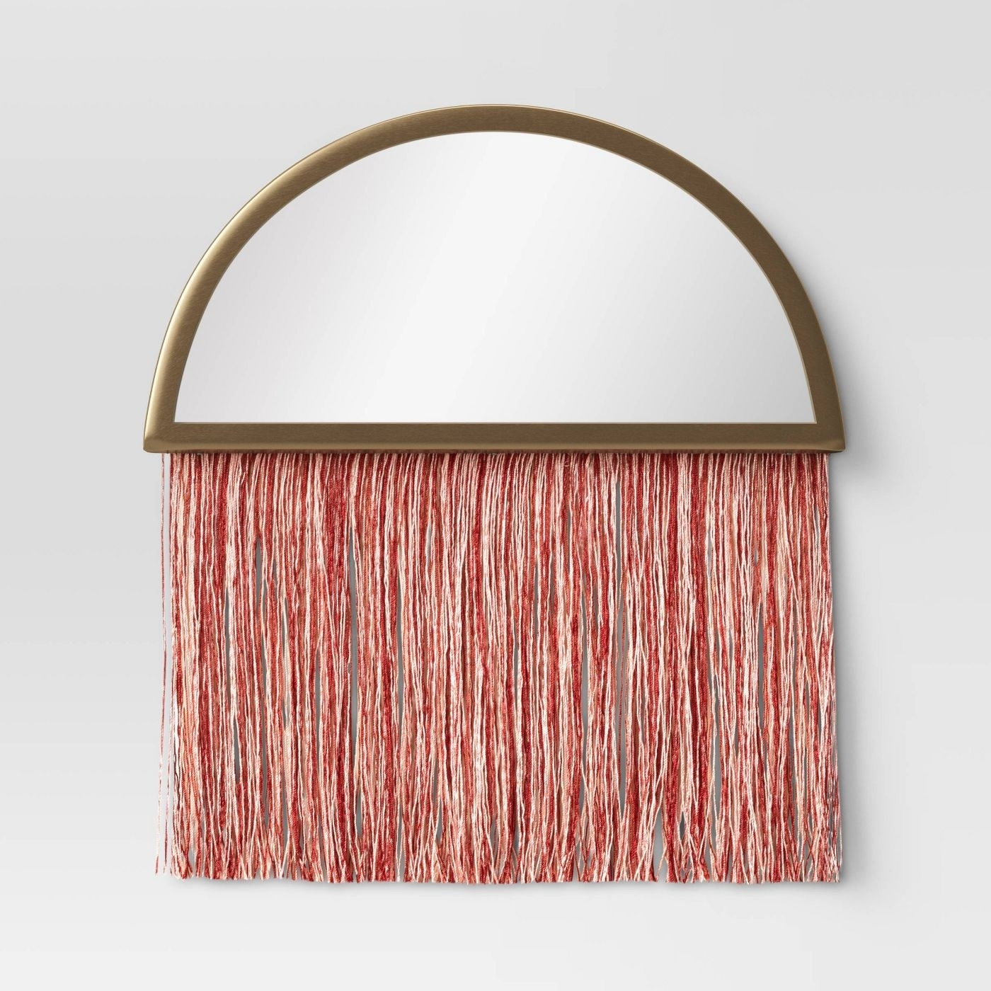 A moon-shaped mirror with pink threads
