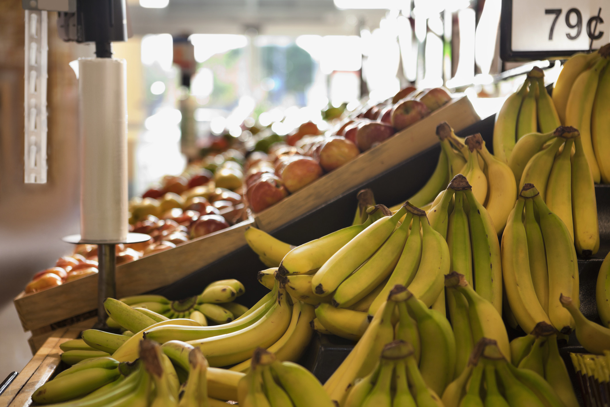 """The produce aisle in a grocery store with a bunch of bananas labeled """"79 cents"""""""