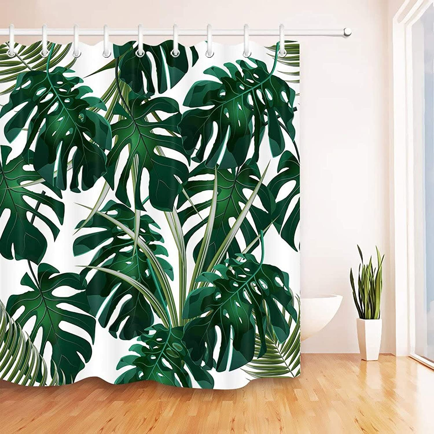 A shower curtain with big tropical leaves printed onto it