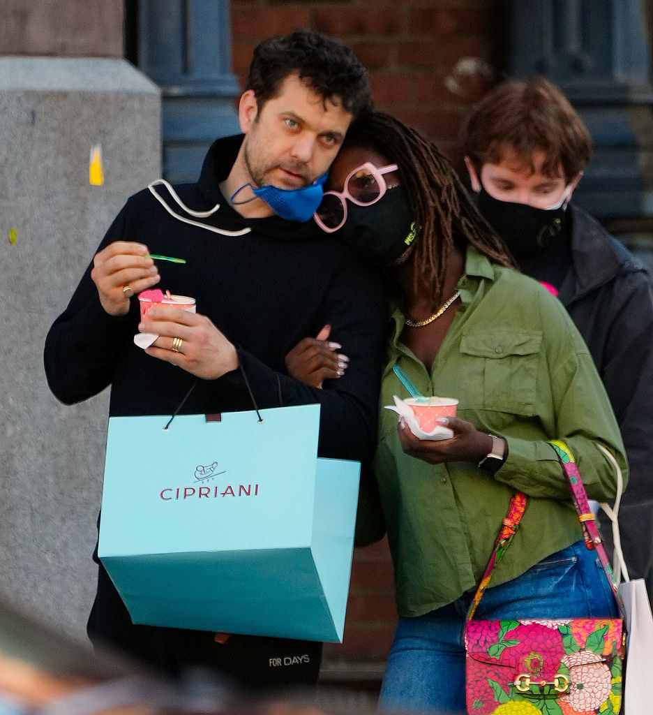 Joshua and Jodie arm-in-arm and holding shopping bags and wearing masks