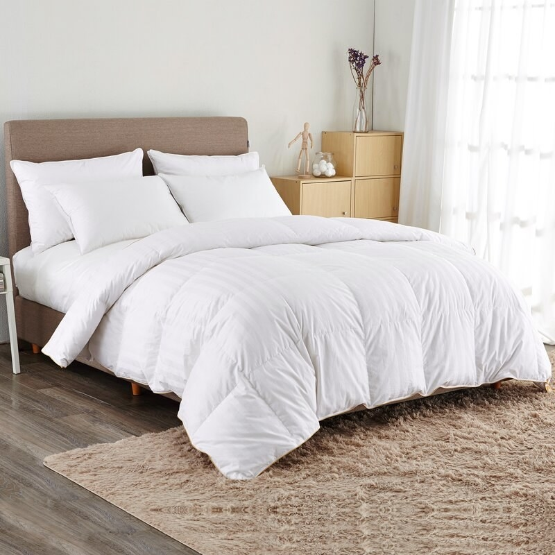 A white, medium weight-goose comforter that can be used during all times of the year