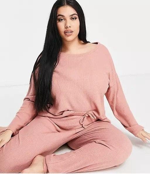 Model wearing pink matching pajama set on white background