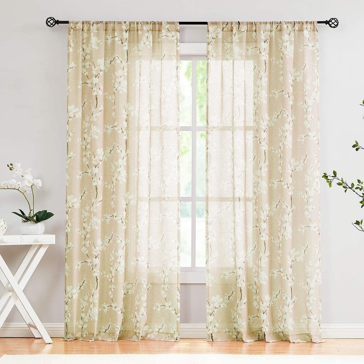 A set of sheer curtains on a bright window with small flowers patterned on them