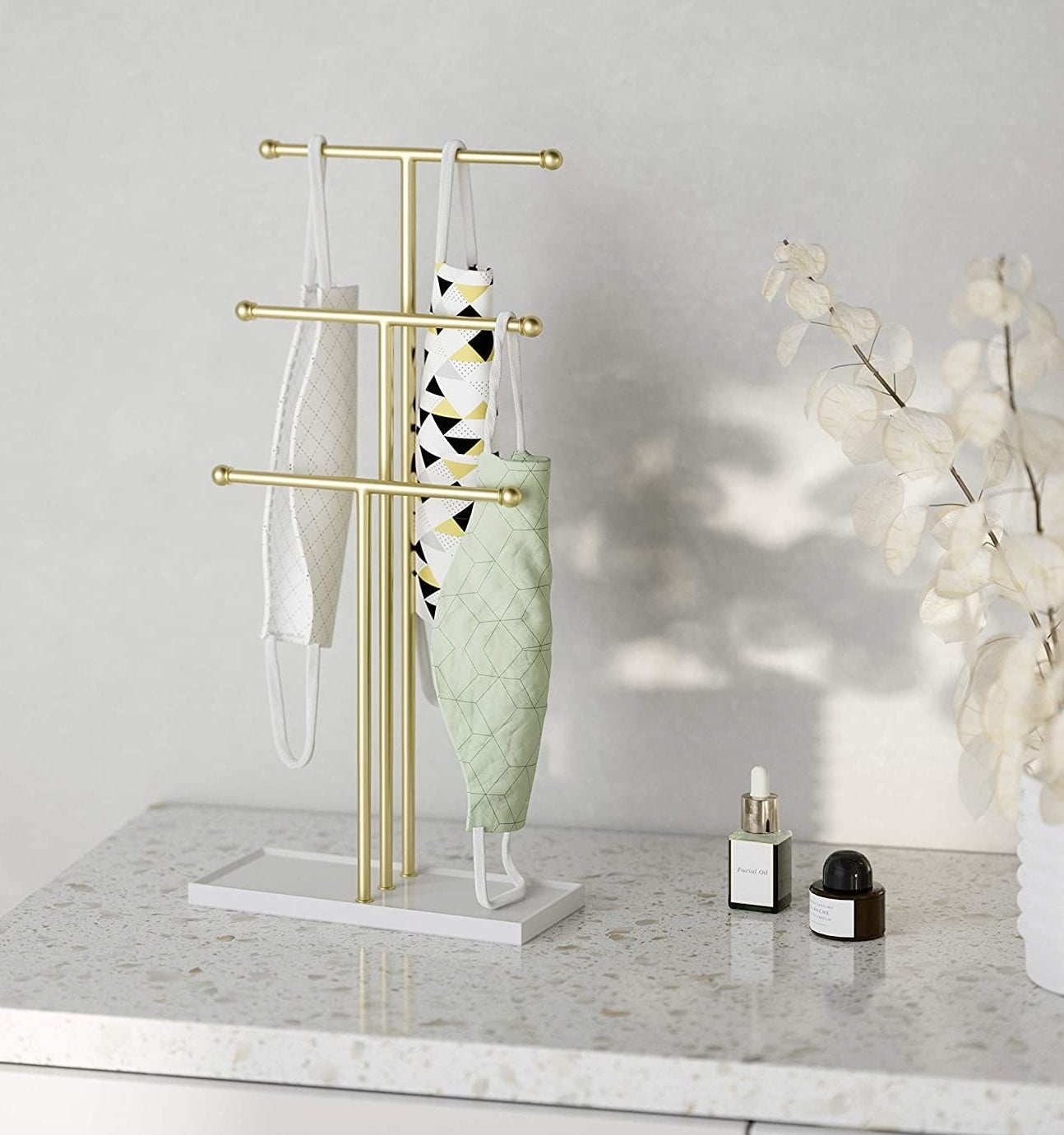 a jewelry stand with face masks hanging off of it