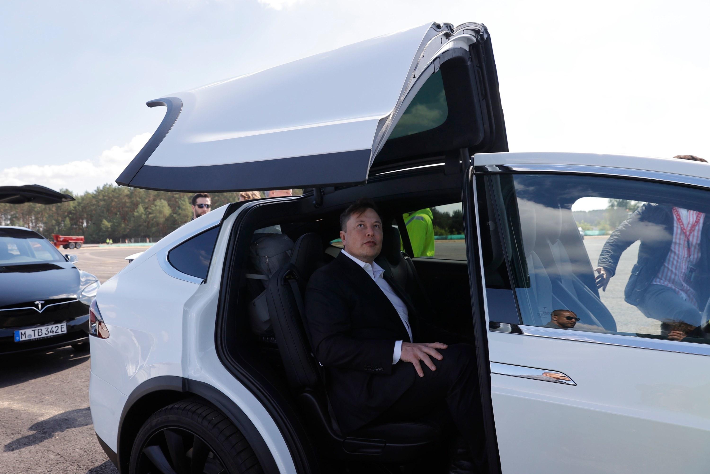 Elon sits inside a Tesla