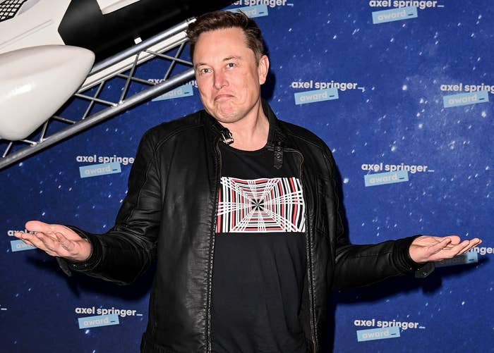 Elon holds his hands out and shrugs
