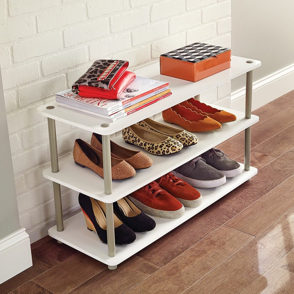 A wooden shoe rack with three shelves that can store up to twelve pairs of shoes