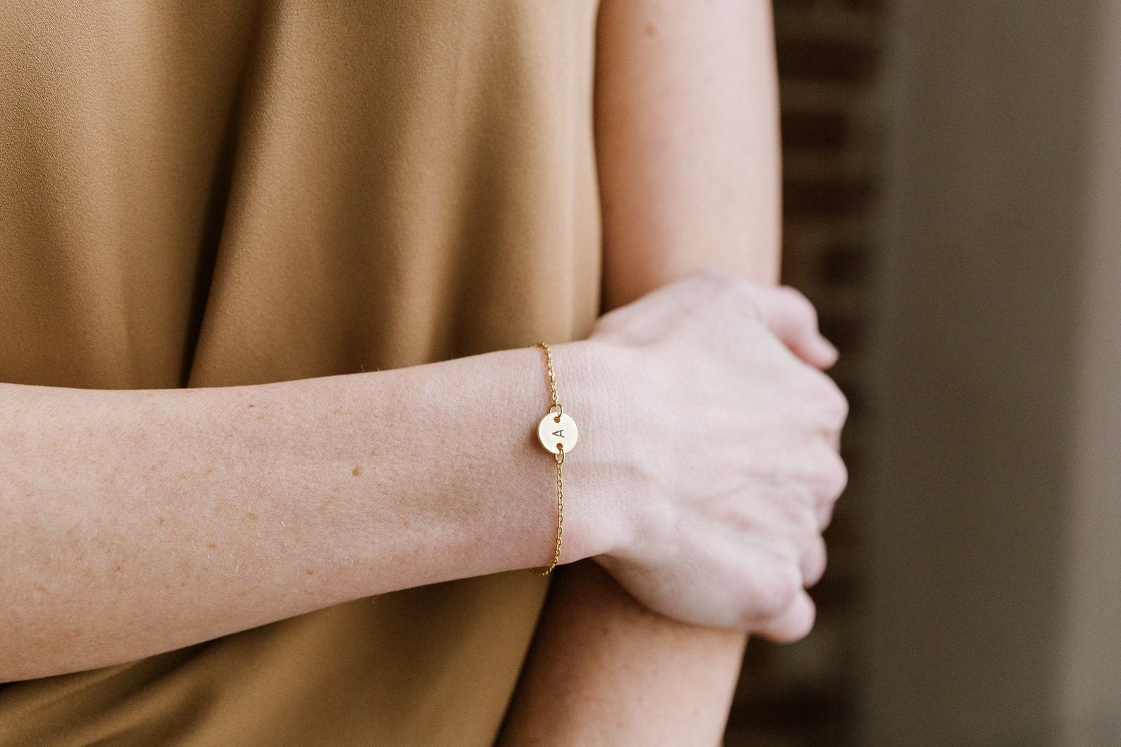 person wearing the initial bracelet