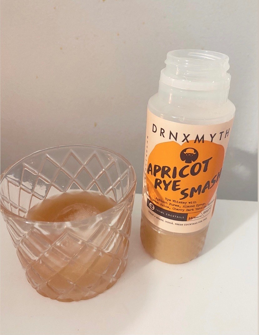 A bottle of Apricot Rye Smash cocktail next to a whiskey glass full of the cocktail
