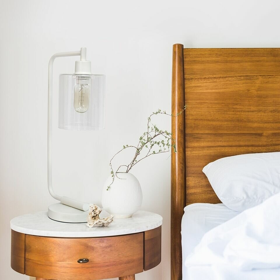 An industrial-style table lamp that has a tubular metal body, a chunky circle pedestal base, and an exposed finial bulb ensconced in a clean-cut cylindrical clear glass shade