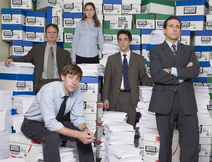 The cast of The Office sit on stacks of paper