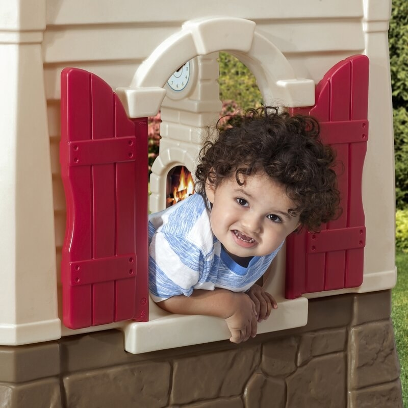 A cottage-style playhouse for outdoors, which contains a flower box, a built-in kitchen, a doorbell, and shingles