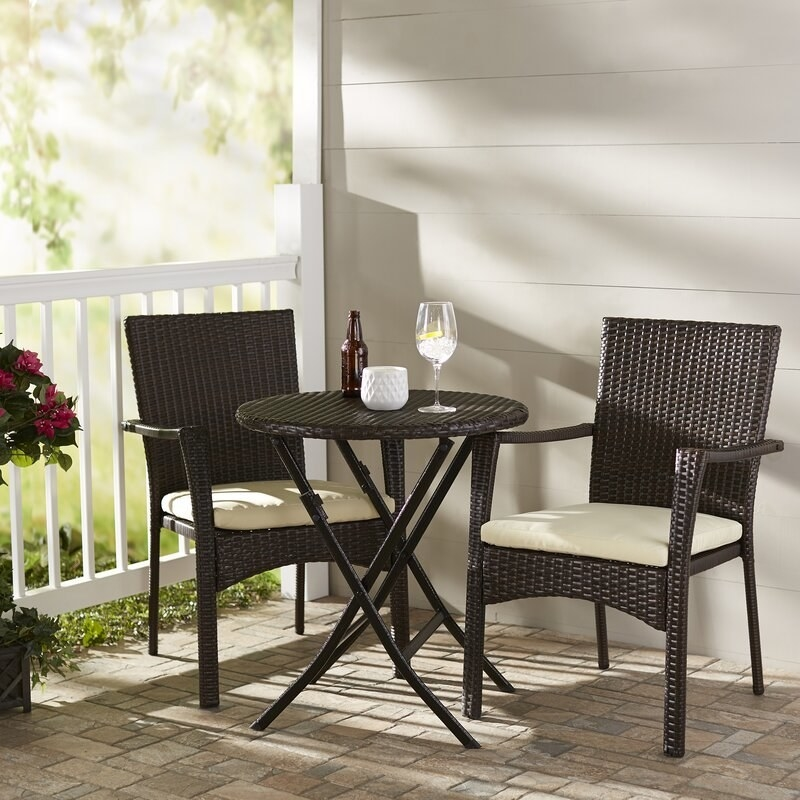 A three-piece, bistro-style patio set that comes with two chairs, two cushions, and a table
