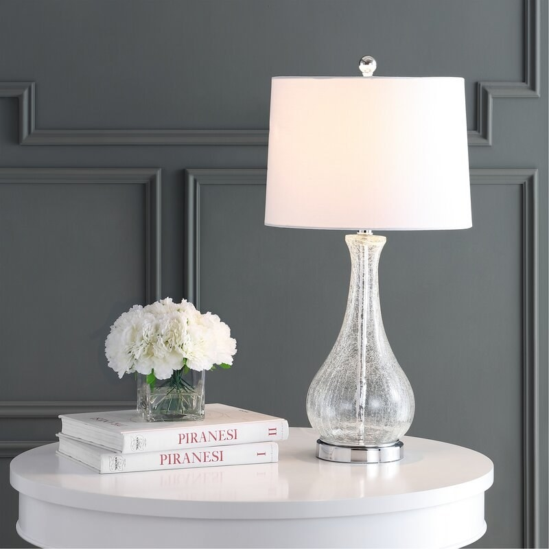 A 27.5-inch table lamp that features a decorative crackled base