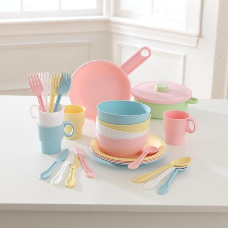A pastel plastic set of kitchen playset with pots, pans, utensils, cups, and plates