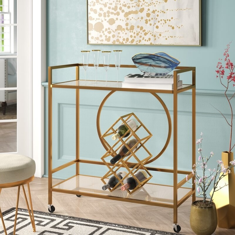 A mirrored bar cart with rolling casters that provides easy storage space to bottles, glasses, and cups