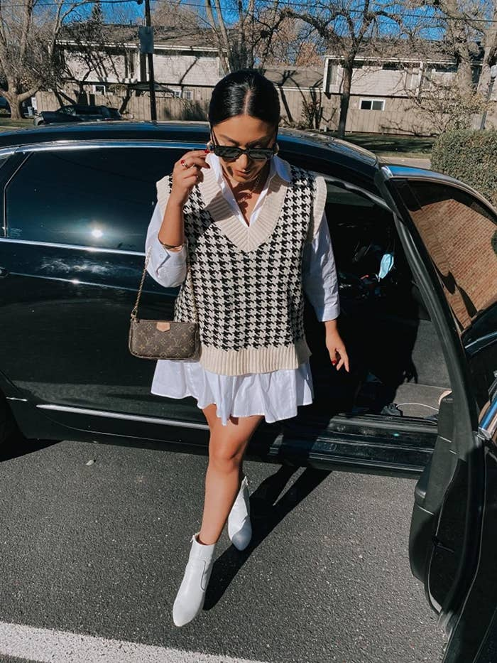 reviewer steps out of a car wearing the oversized houndstooth knitted vest over a white shirt-dress