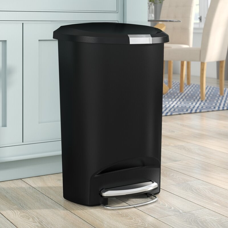 A plastic, step-on garbage can that can store up to 13 gallons worth of food waste