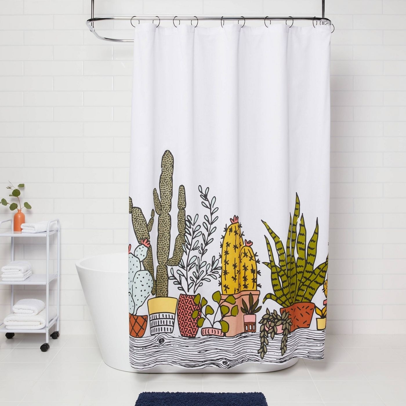 white shower curtain with plant design hanging over a tub