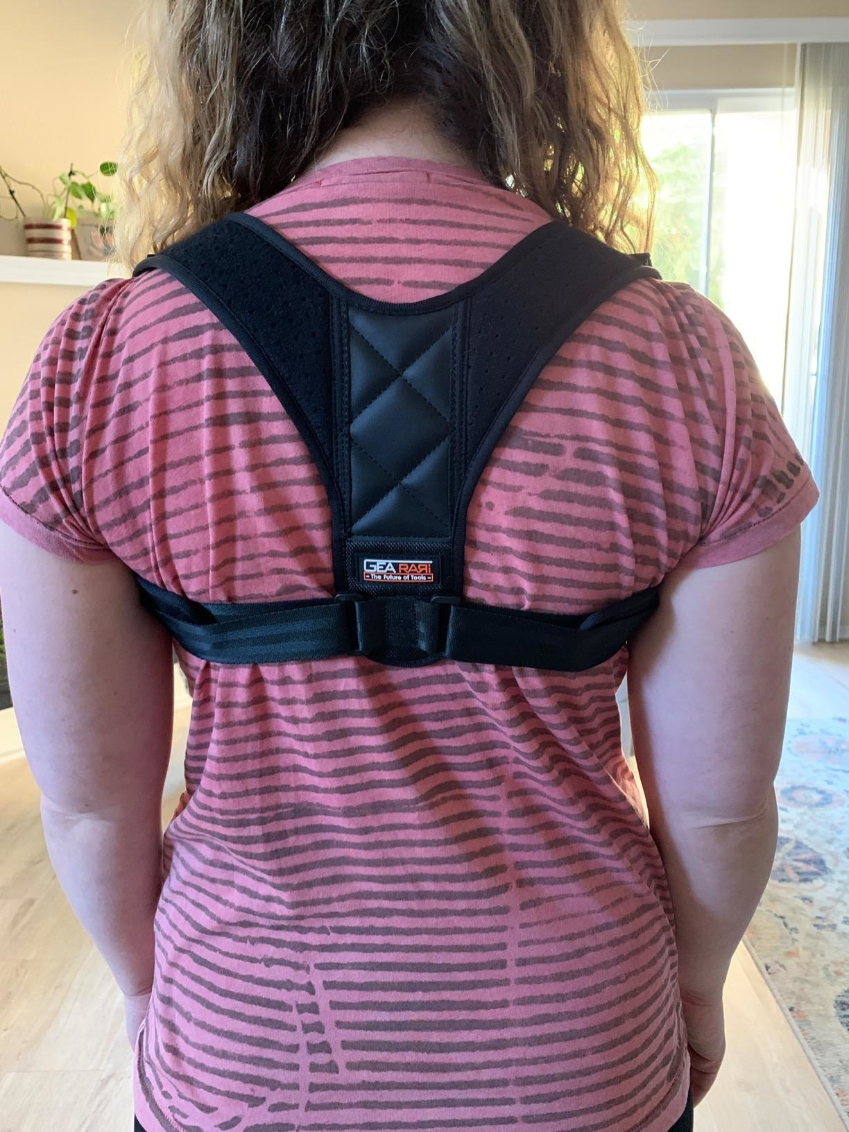 Reviewer wearing the brace over their T-shirt