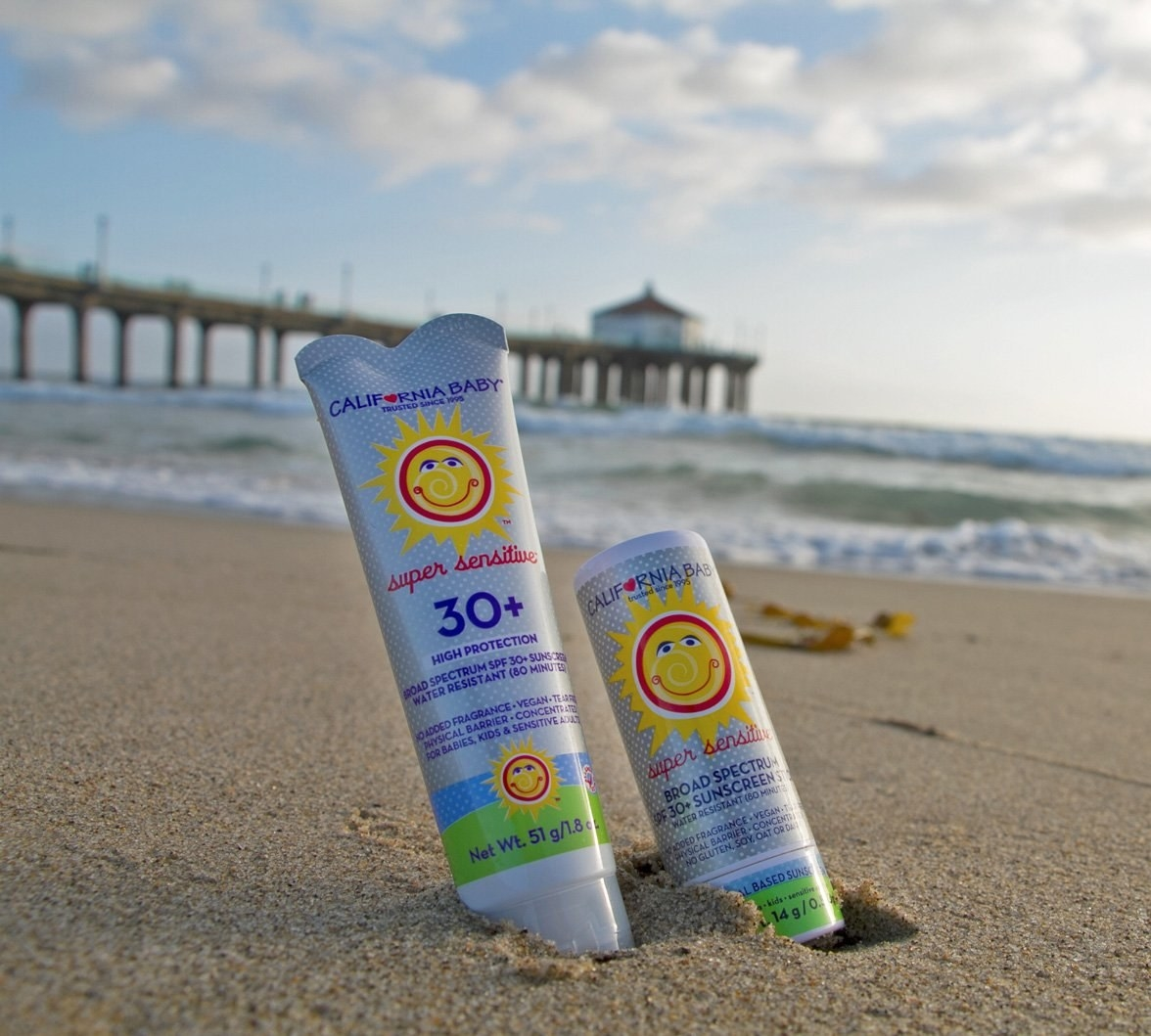 bottle of california baby super sensitive SPF 30+ sunscreen on the beach