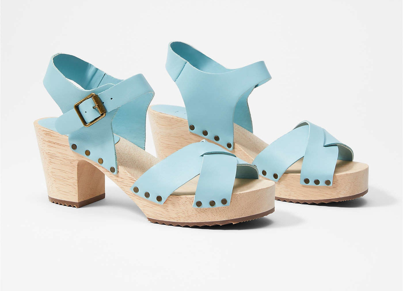 the tan wood platform clogs with blue criss-cross straps across the toe and buckle ankel strap