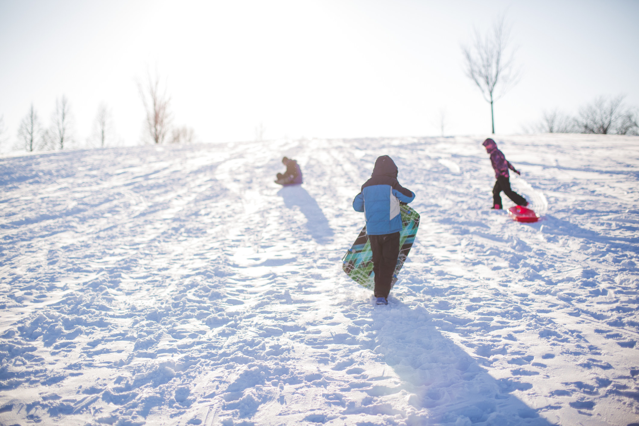 Three kids playing in snow.