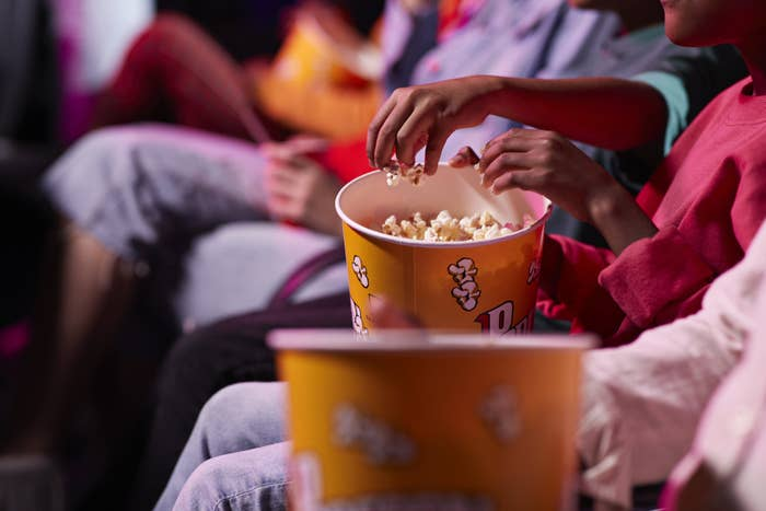 People eating popcorn at a movie theater.