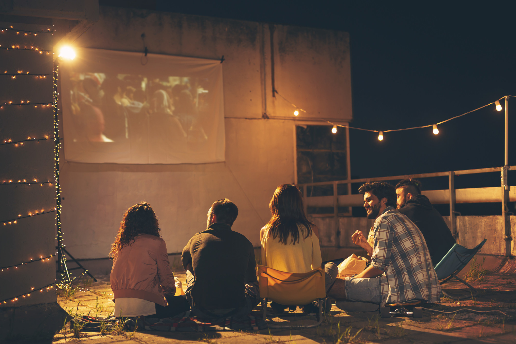 Friends watching a movie on a projector screen.