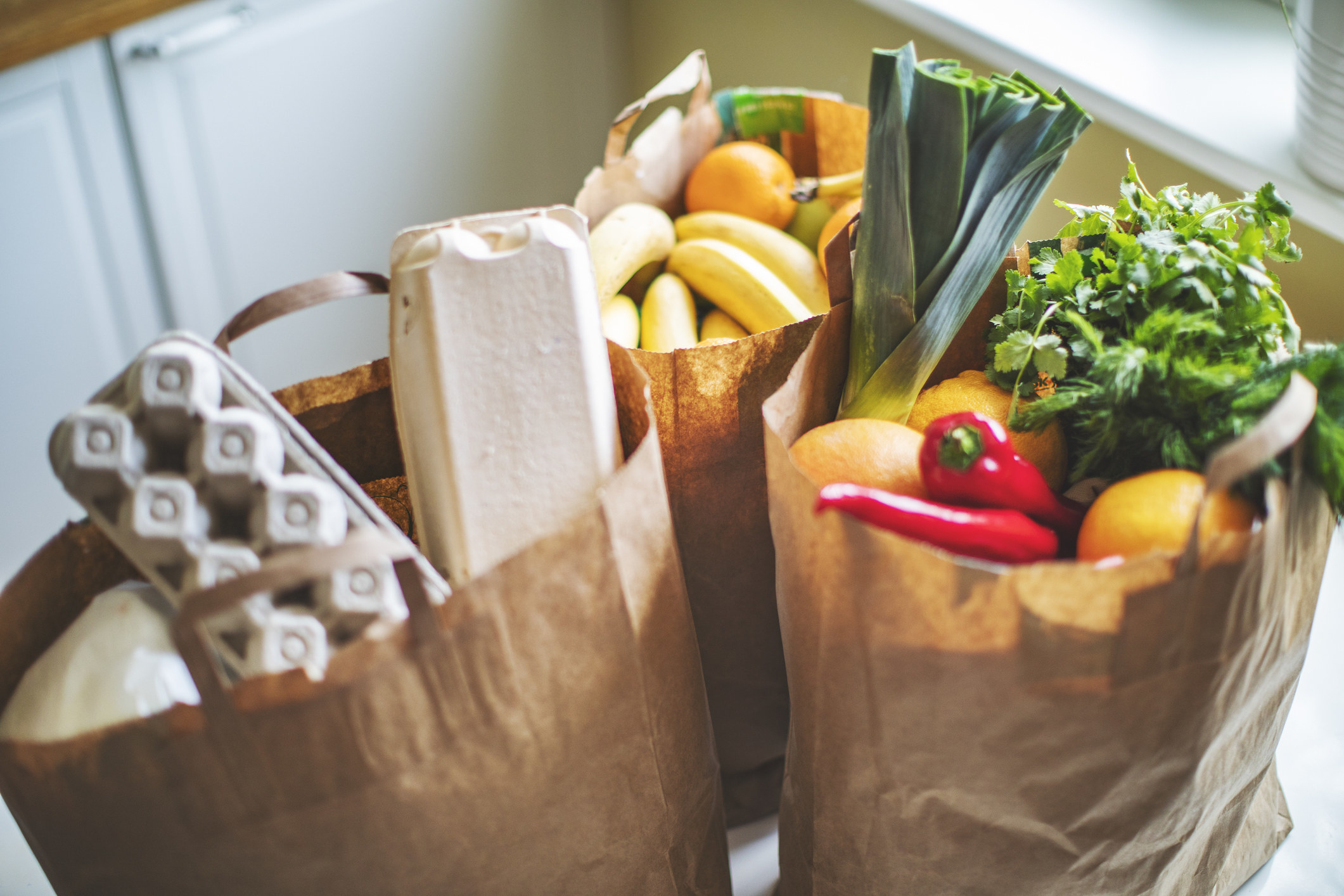 Grocery bags full of produce and eggs.