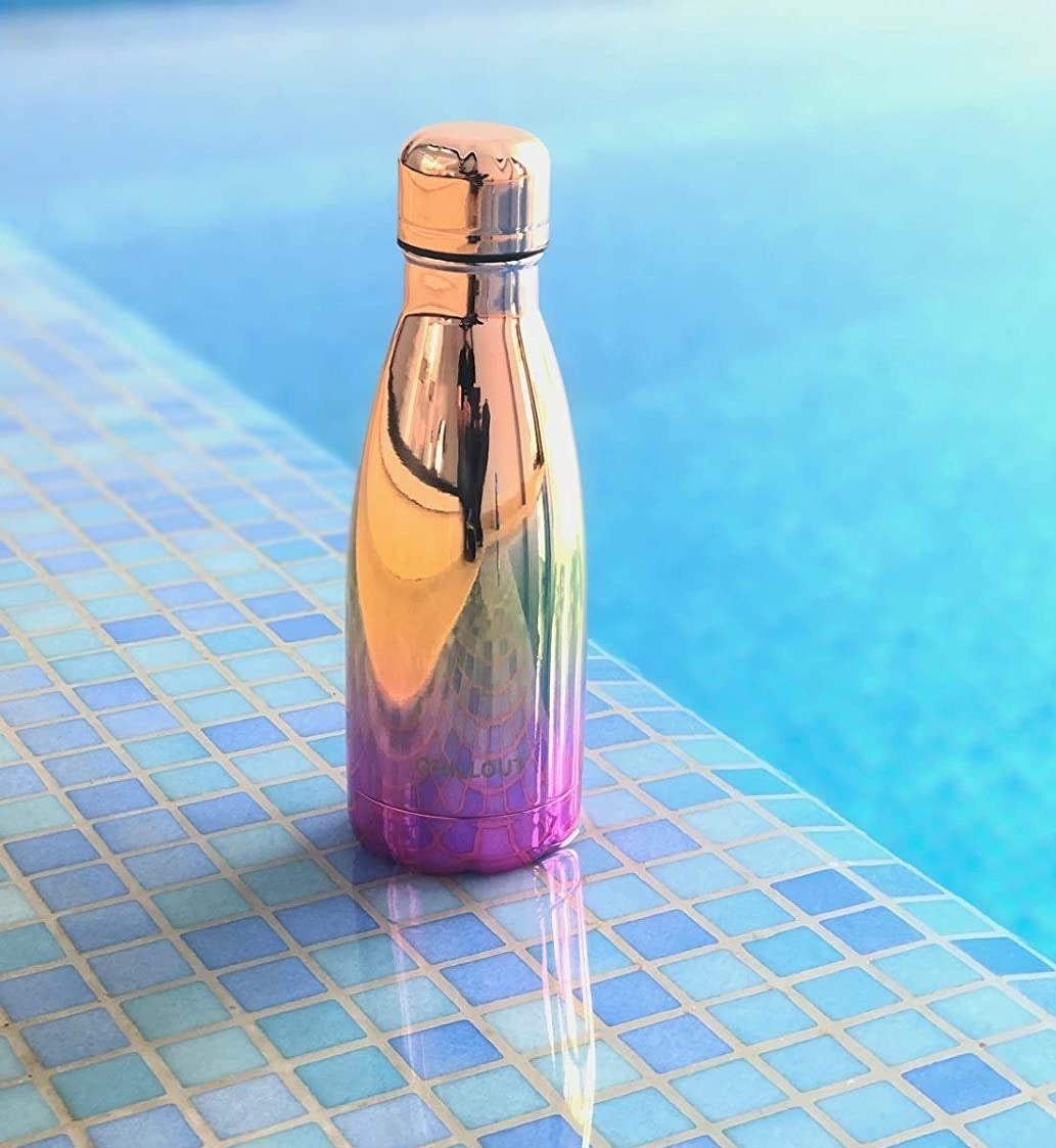 The shiny waterbottle on the edge of a pool