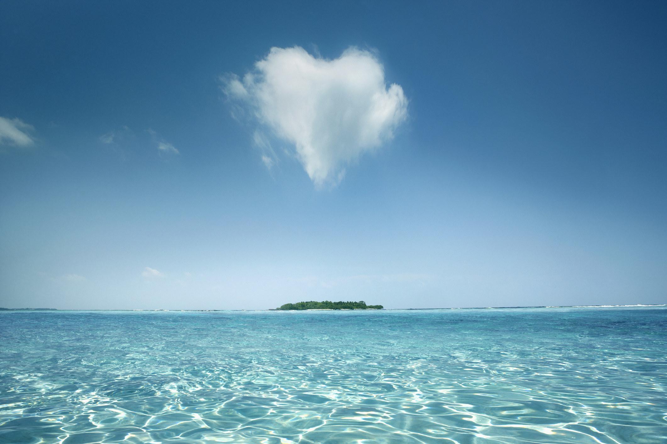 An image of a heart-shaped cloud above an ocean