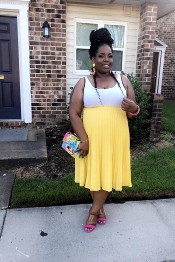 reviewer wearing the skirt in yellow with a white tank and heels
