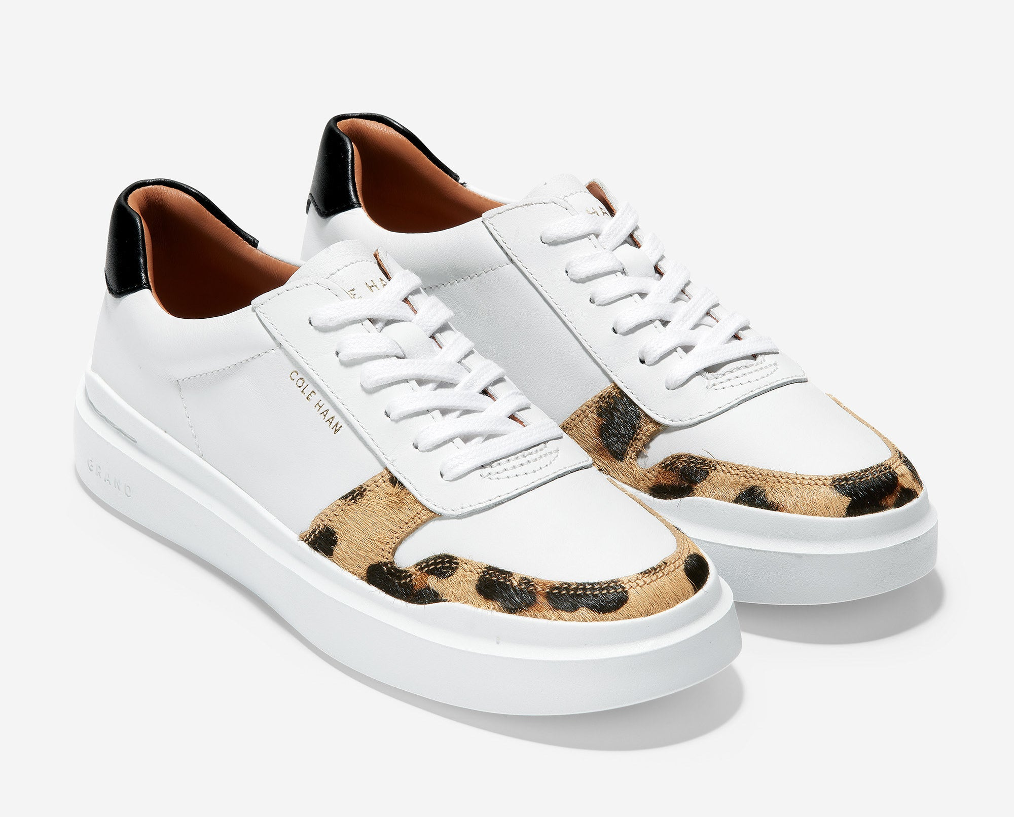 the white sneakers with strip of leopard print around the toe and black by the heel