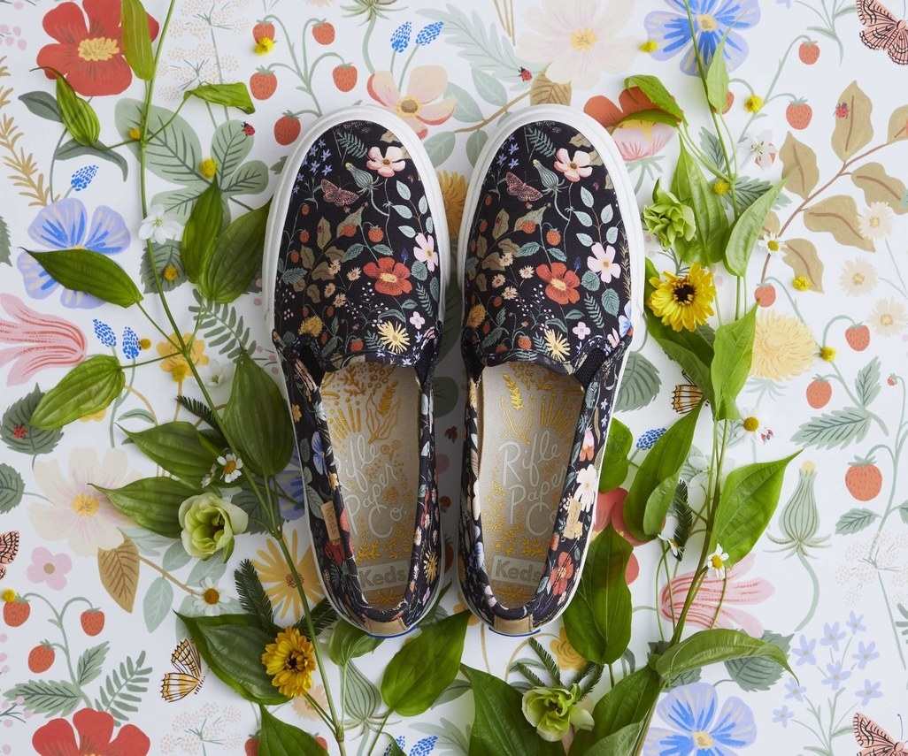black slip-on sneaker-style shoe with floral print and white sole