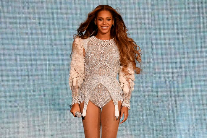 Beyoncé performs onstage in a white embellished outfit