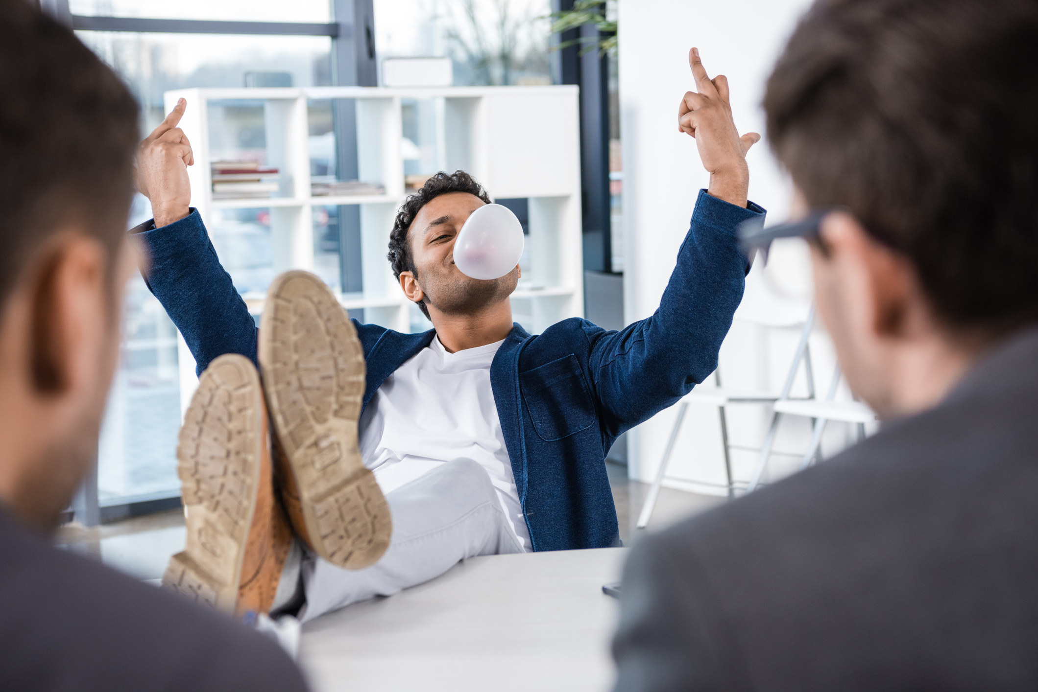 businessman blowing bubble gum and showing middle fingers during job interview