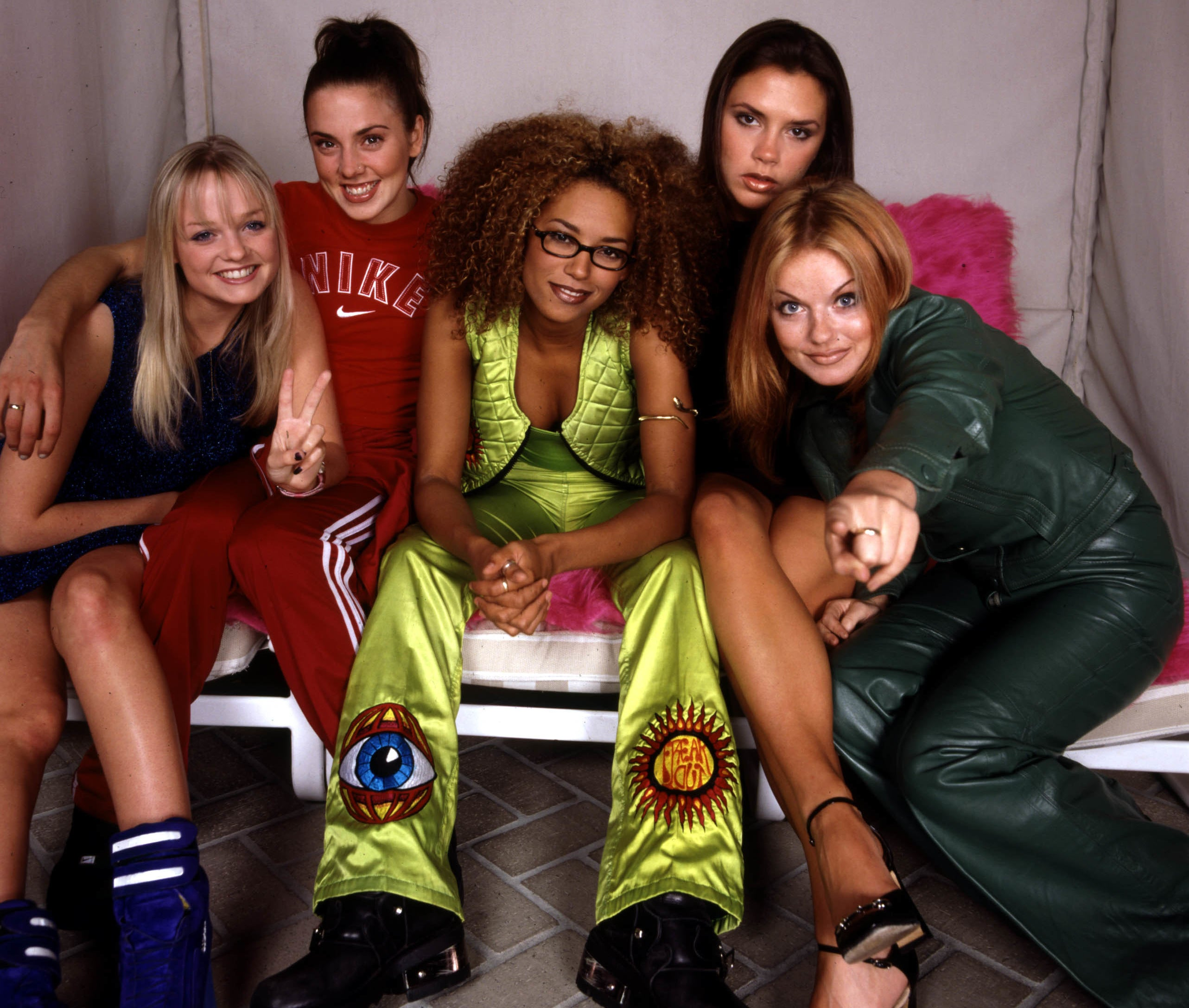 The Spice Girls sit on a pink fuzzy couch