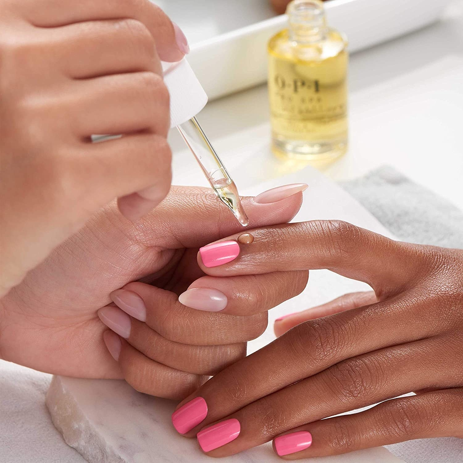 a person applying a drop of nourishing oil to someones cuticle