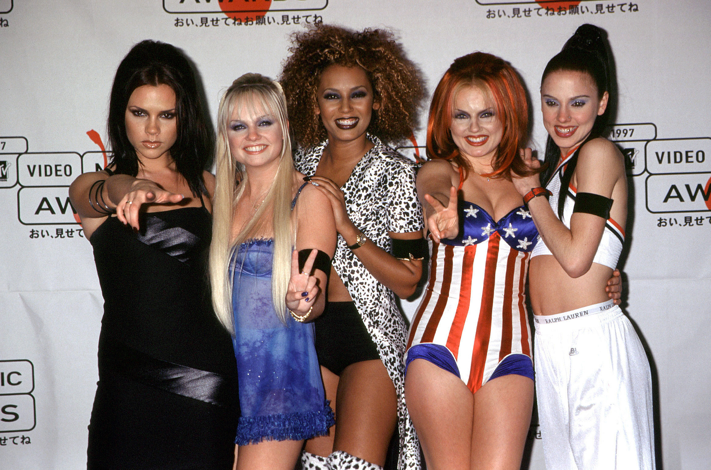 The Spice Girls hold up peace signs on a red carpet