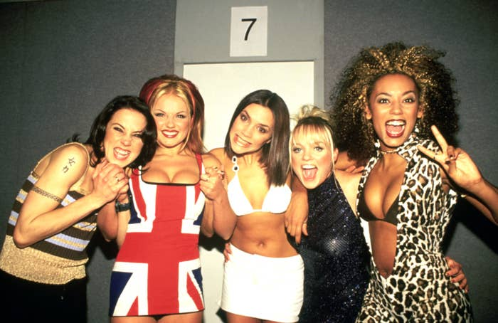 The Spice Girls hold hands while posing together