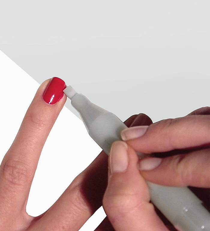 A person cleaning up the sides of their freshly painted finger nails