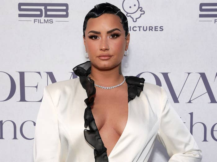 Demi poses in a white, deep V-neck silk shirt at the premiere of her documentary