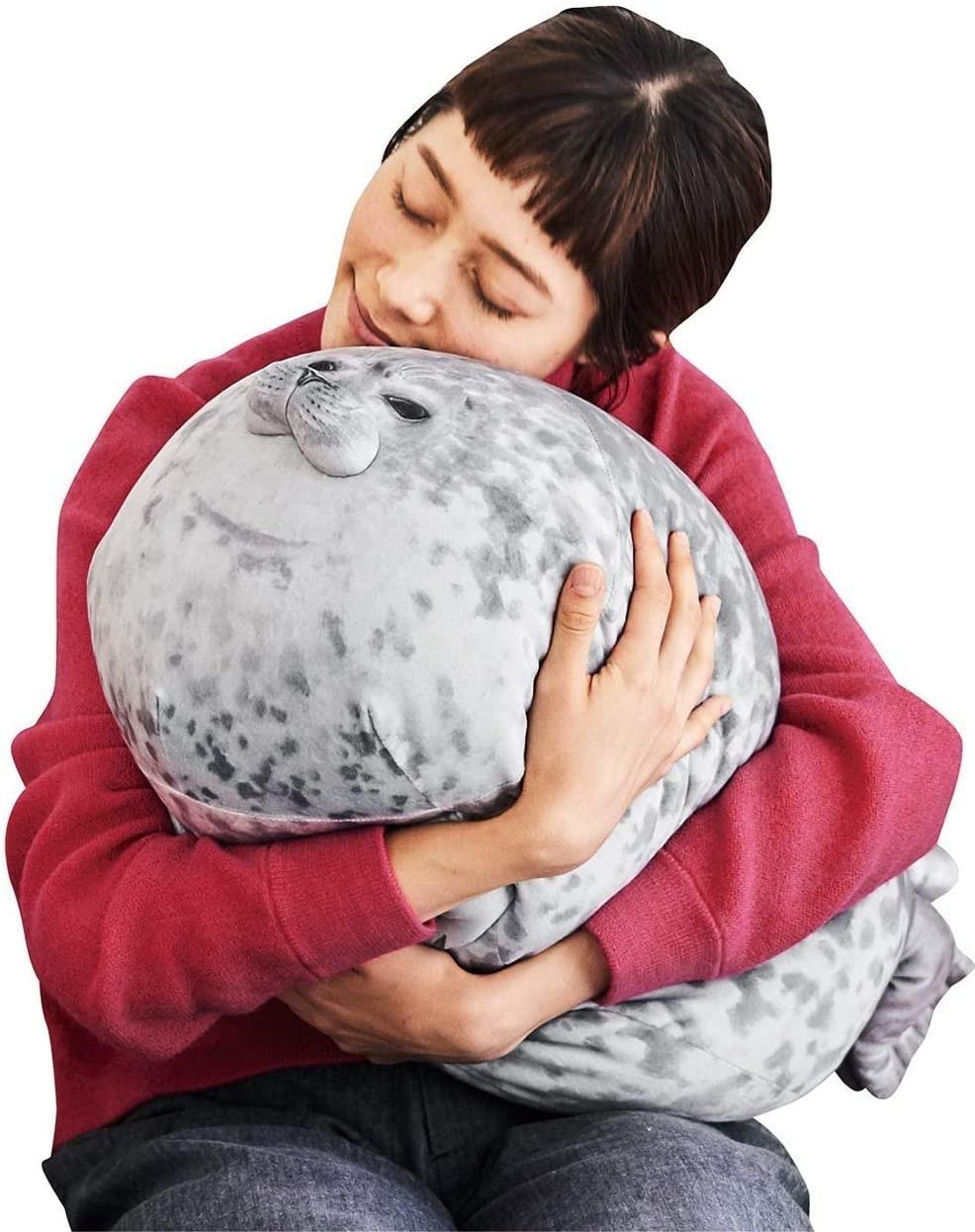 A model hugs the stuffed seal