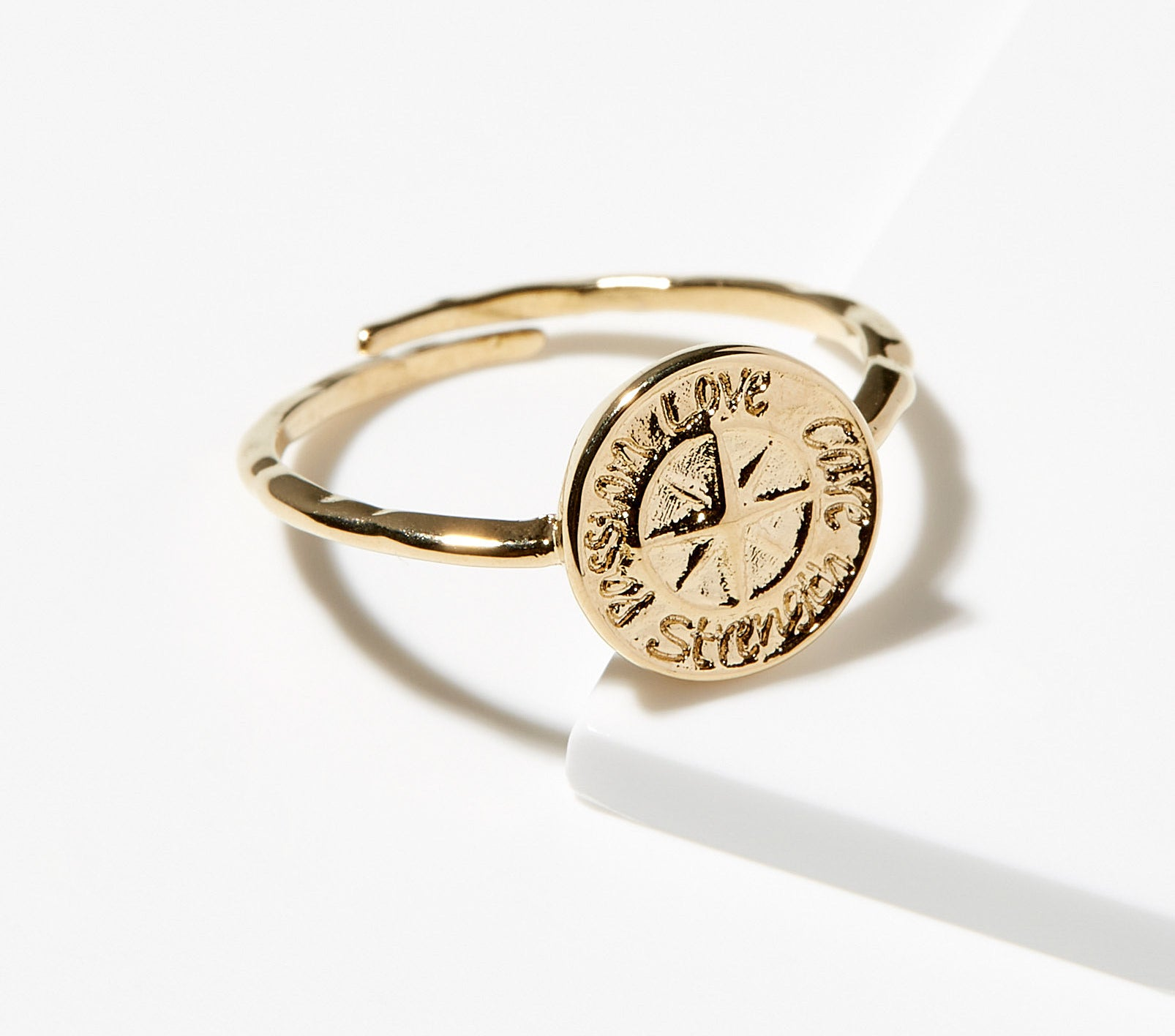 A gold ring with an engraved compass rose that have the words passion love strength care written around it