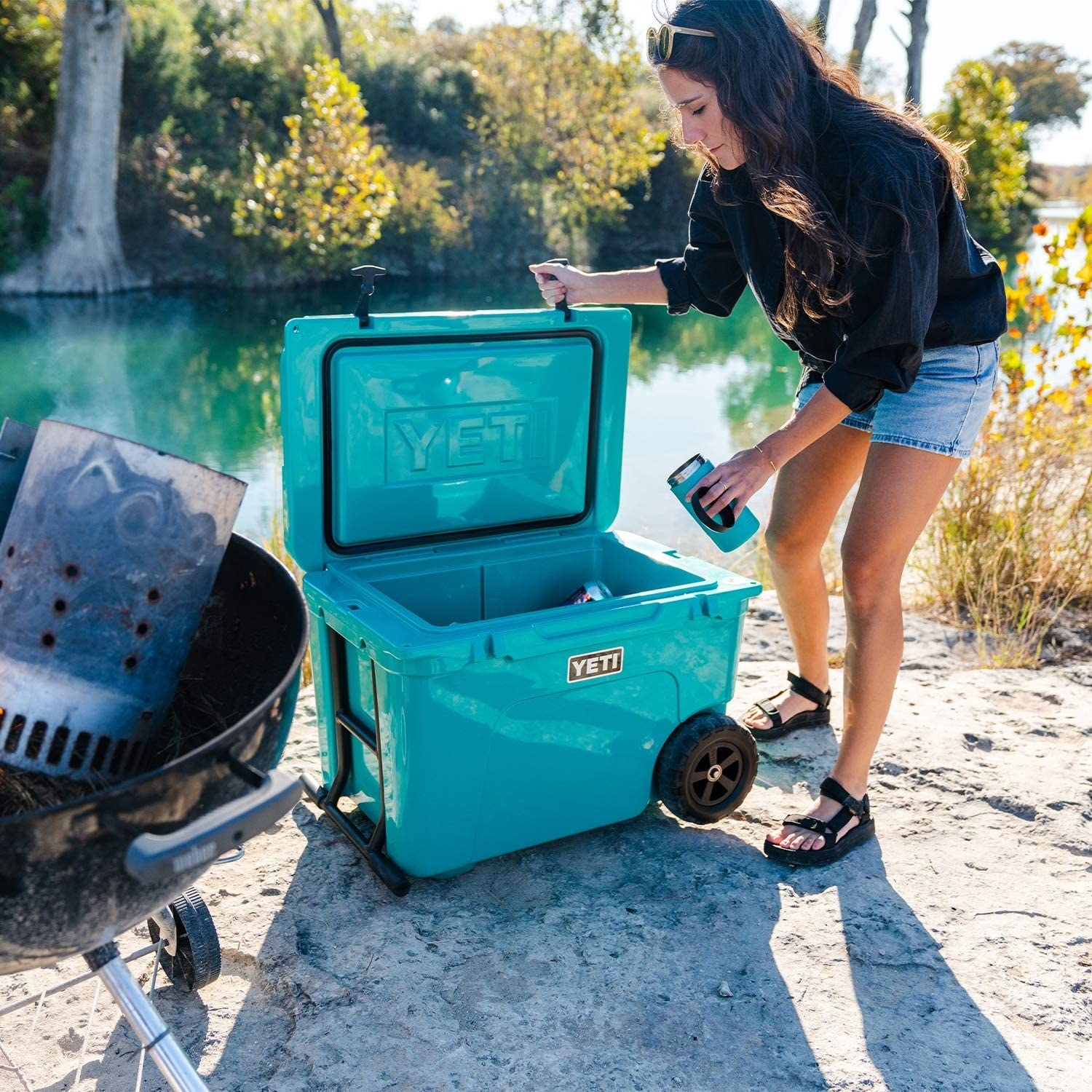 A model takes a drink out of the blue cooler