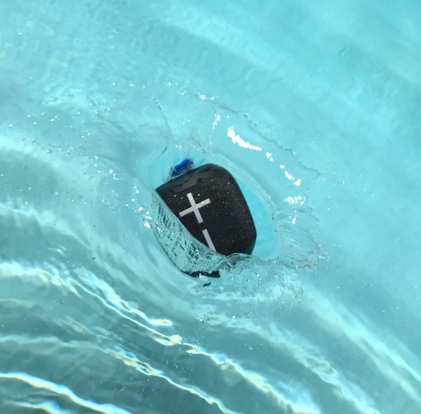 A black speaker floats in a reviewer's pool