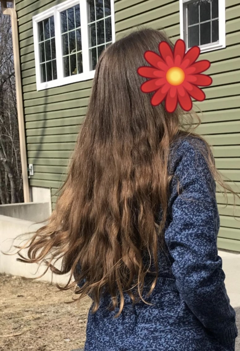 a person with long, shiny, and wavy hair after using this mask for a year